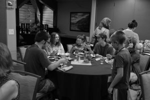 Siblings eating around a table at the 2019 Family Conference